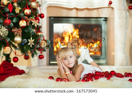 Adorable toddler girl lies on the fur and dreams about the gifts for the new year behind her a Christmas tree and lit fireplace  - stock photo