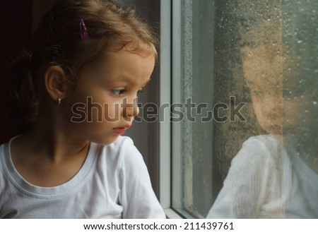 Adorable toddler girl looking at raindrops on the window  - stock photo