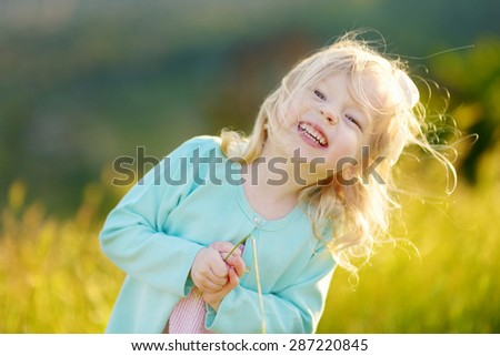 Adorable toddler girl on warm and sunny summer day - stock photo