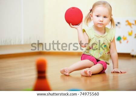 Adorable toddler girl playing bowling at home - stock photo