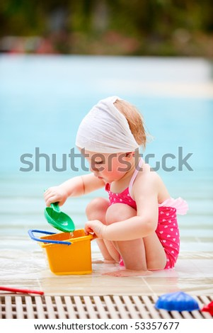 Adorable toddler girl playing in swimming pool - stock photo