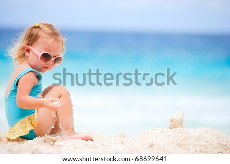 Adorable toddler girl playing on white sand beach - stock photo