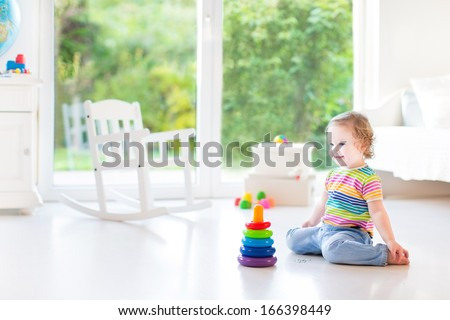 Adorable toddler girl playing with a colorful pyramid in a beautiful white room with a big window into the garden - stock photo
