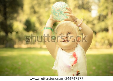 Adorable toddler girl playing with blue ball in the park. Hippie style. Many friendship bracelets. Unusual coulomb. Natural light.