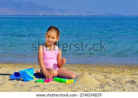 Adorable toddler girl playing with her toys at beach - stock photo