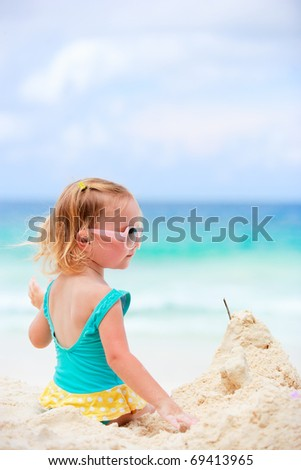 Adorable toddler girl playing with sand on tropical beach - stock photo