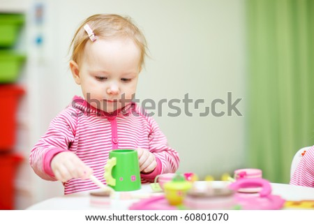 Adorable toddler girl playing with wooden teapot and cups  at home - stock photo