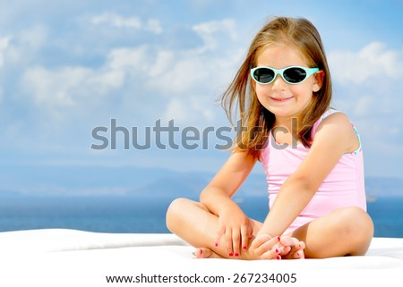 Adorable toddler girl relaxing on sunbed - stock photo