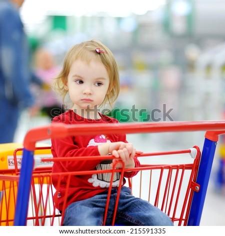 Adorable toddler girl sitting in shopping cart - stock photo