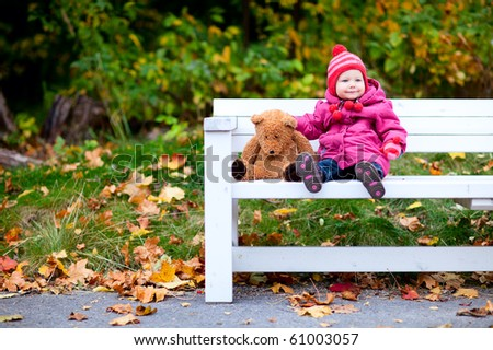 Adorable toddler girl sitting on bench in autumn park - stock photo