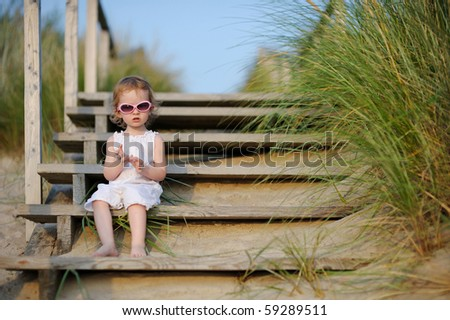 Adorable toddler girl sitting on the stairs by the sea - stock photo