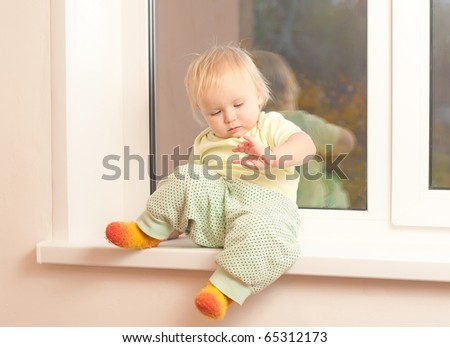 Adorable toddler girl sitting on the window sill