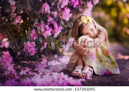 Adorable toddler girl sitting under blooming tree at sunny spring day. Kid and flower. - stock photo