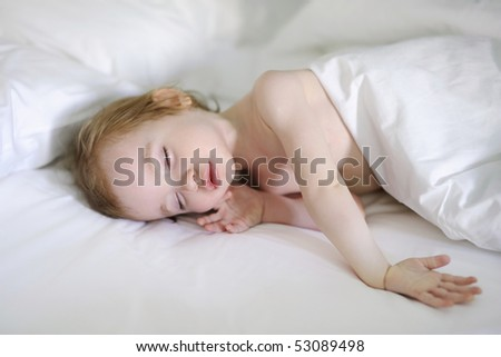 Adorable toddler girl sleeping in a bed - stock photo