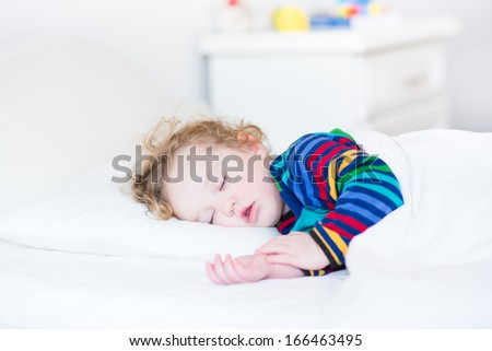 Adorable toddler girl taking a nap in a white sunny bedroom - stock photo