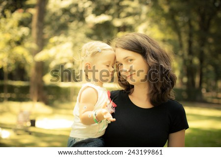 Adorable toddler girl touching her Mom in the park. Eyes closed. Summer Colorful natural light - stock photo
