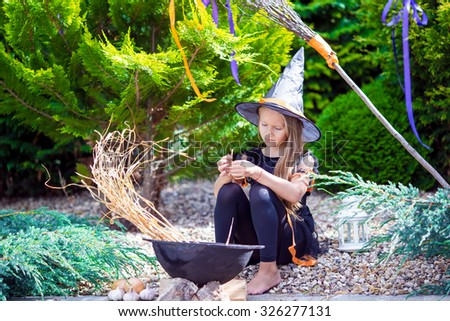 Adorable toddler girl wearing witch costume on Halloween outdoors. Trick or treat. - stock photo