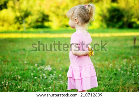 Adorable toddler girl with curly blond hair wearing a pink dress playing outdoors on beauty summer day  - stock photo