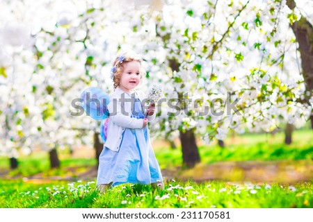 Adorable toddler girl with curly hair and flower crown wearing a magic fairy costume with a blue dress and angel wings playing in a sunny blooming fruit garden with cherry blossom and apple trees - stock photo