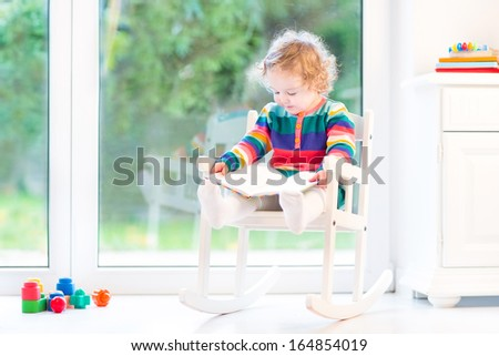 Adorable toddler girl with curly hair wearing a colorful knitted dress reading a book and relaxing in a white rocking chair at home next to a big window - stock photo