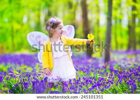 Adorable toddler girl with curly hair wearing a fairy costume with purple wings and yellow dress is playing in a beautiful spring forest with fresh blooming bluebell flowers on a sunny day in Germany  - stock photo