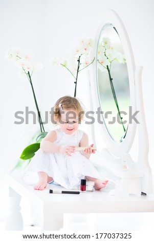 Adorable toddler girl with curly hair wearing a white dress playing with make up and cosmetics in front of a round mirror in a white sunny bedroom - stock photo