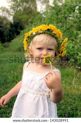 Adorable toddler girl with dandelion wreath on her head smelling the yellow flower - stock photo