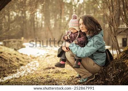 Adorable toddler girl with Mom sitting on the ground in the park. Cold spring. Shiny stream background. Forest without leaves. - stock photo