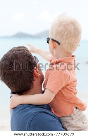 adorable toddler hugging his father and pointing the finger - stock photo