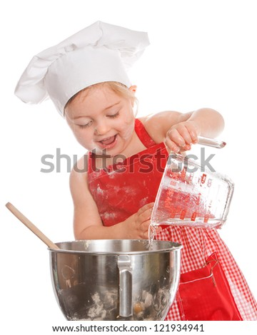 Adorable toddler in chefs hat and red apron pouring liquid into a mixing bowl.  Isolated on white. - stock photo