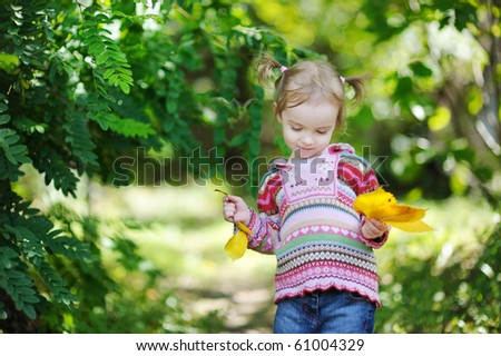 Adorable toddler in early autumn park