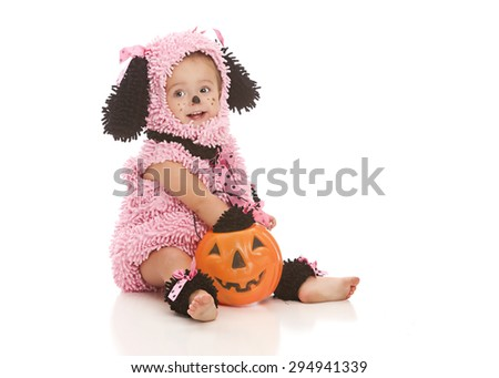 Adorable toddler in her pink puppy Halloween costume, sitting on the floor with her candy from trick or treating.  Isolated on white.   - stock photo