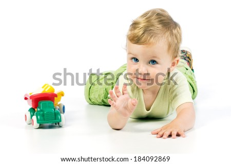 Adorable toddler lying on the floor beside his plastic toys - looking directly at camera with his beautiful blue eyes and waving to photographer. - stock photo