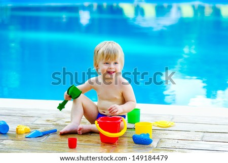 Adorable toddler playing with toy bucket and spades set by the swimming pool with blue water - stock photo