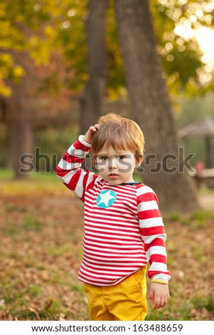 Adorable toddler scratching his head in confusion - stock photo