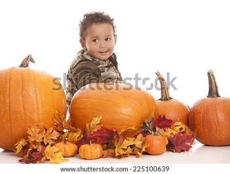 Adorable toddler sitting on a large pumpkin.  Isolated on white with room for your text.