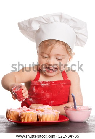 Adorable toddler wearing a chef's hat and red apron decorating cupcakes.  Isolated on white. - stock photo