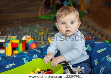 Adorable toddler with blue eyes and blond hair playing with toy indoor