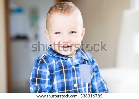 adorable toddler with blue eyes smiling and enjoying time at home