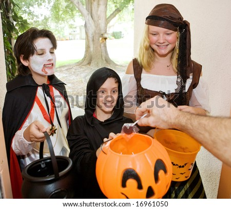 Adorable trick or treaters in the doorway waiting for candy. - stock photo