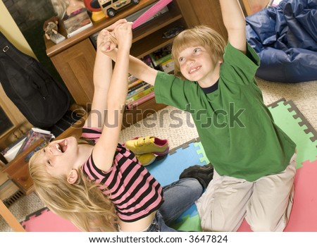 Adorable twins wrestling/playing keep-away on the playroom floor. - stock photo