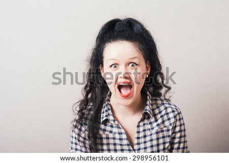 Adorable woman with red lipstick standing in awe looking at camera with mouth and eyes open wide surprised - stock photo