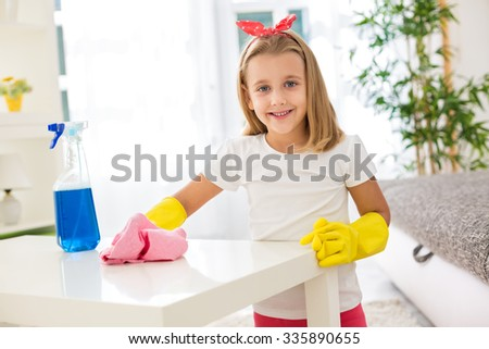 Adorable worth girl holding pom and cleaning a table at room - stock photo
