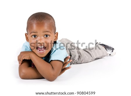 Adorable 3 year old black or African American boy lying on the floor looking very surprised - stock photo