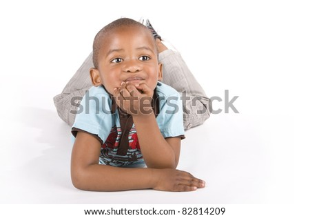 Adorable 3 year old black or African American boy lying with his left hand on his chin
