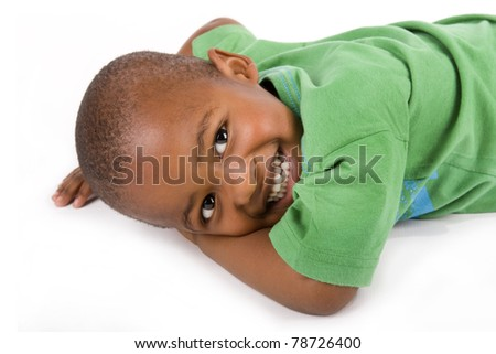 Adorable 3 year old black or African American boy with a smile lying on the floor looking at you - stock photo