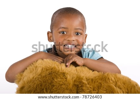 Adorable 3 year old black or African American boy with a toy bear smiling very happily