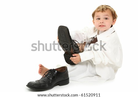 Adorable 3 year old blond american boy putting on dad's big shoes.