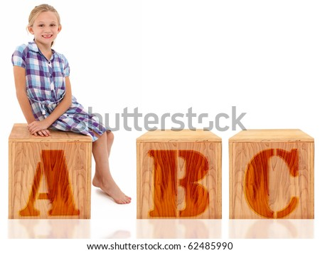 Adorable 7 year old blond american girl sitting on wooden box over white background. Letters ABC. - stock photo