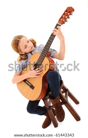 Adorable 7 year old blond girl playing acoustic guitar over white background. - stock photo